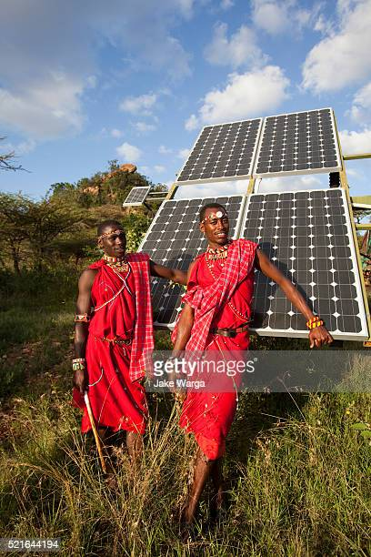 Maasai men standing in front of solar panels