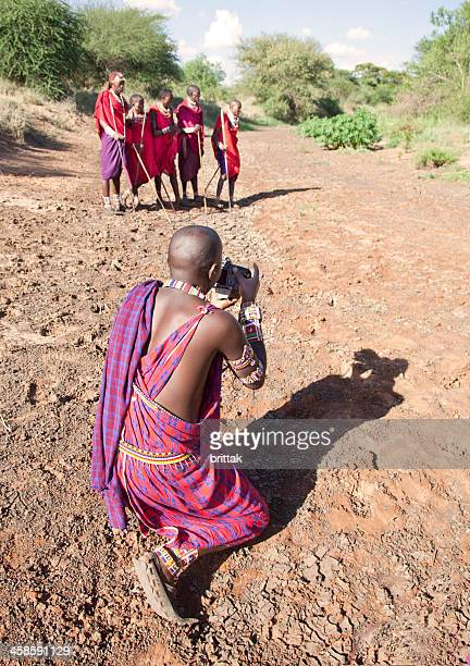 maasai taking pictures of his friends in strong sunlight - eastern african tribal culture stock photos and pictures