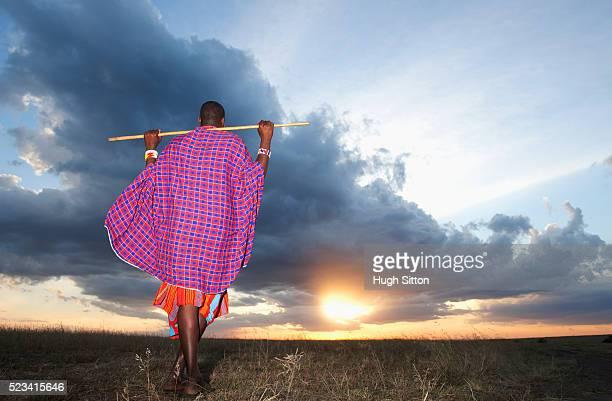 Maasai tribesman standing looking at setting sun, in the Maasai Mara game reserve. Kenya