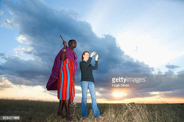 Maasai tribesman standing with tourist in the Maasai Mara game reserve, Kenya