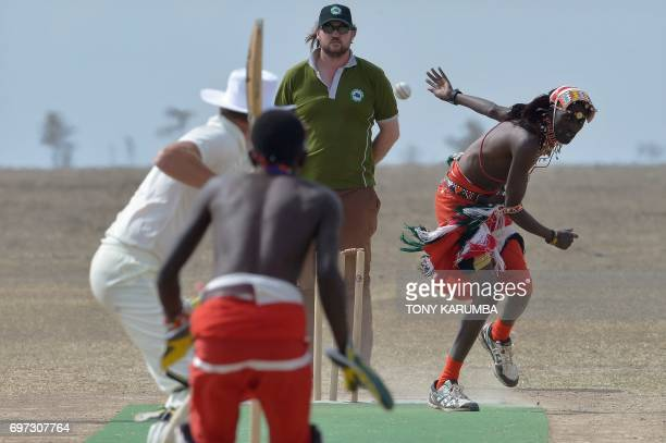 A maasai warrior bowls a cricket ball against an opponent from the British Army Training Unit Kenya team on June 18 2017 during a cricket tournament...