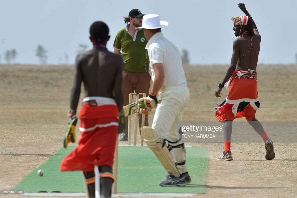 A maasai warrior celebrates after bowling a cricket ball against an opponent from the British Army Training Unit Kenya (BATUK) team on June 18, 2017 during a cricket tournament played in the wilds of Laikipia county's Ol-Pejeta Conservancy, at the foot of Mount Kenya, and home to the last three northern white rhino sub-species on the planet. The two-day tournament dubbed 'Last Male Standing' is an annual charity event that aims to raise awareness of the plight of the nothern-white rhino and creates funding to continue ongoing research into ways to save the sub-species from extinction. /