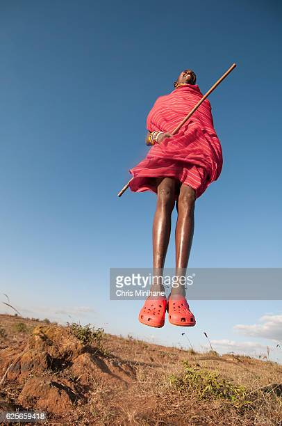 maasai warrior moran tribesman jumping wearing traditional dress - masai fotografías e imágenes de stock