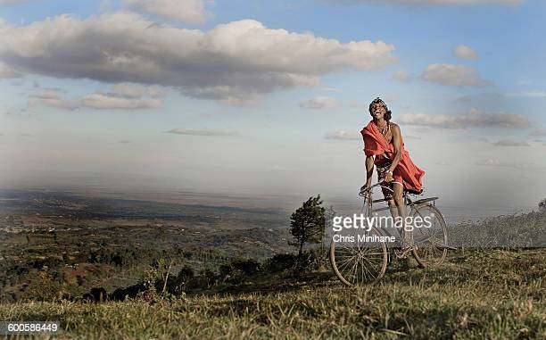Maasai Warrior Rides a bike atop the hills, Kenya