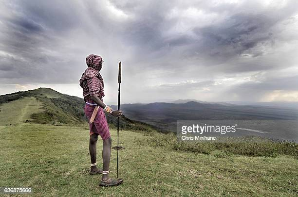 maasai warrior standing over a beautiful scenic view - african tribal culture stock pictures, royalty-free photos & images
