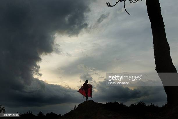 maasai warrior with back lit red blanket and dramatic sky - guerrier massai photos et images de collection