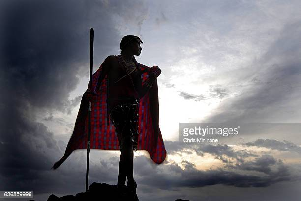 maasai warrior with back lit red blanket and dramatic sky - 民族衣装 ストックフォトと画像