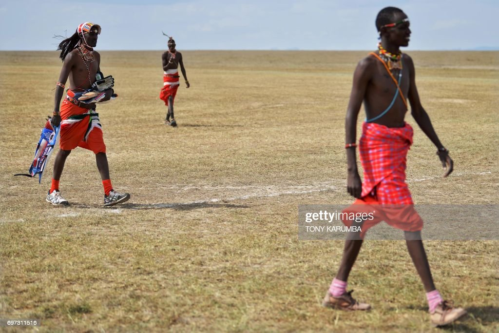 Maasai warriors leave the pitch following a match against the British Army Training Unit Kenya (BATUK) team on June 18, 2017 during a cricket tournament played in the wilds of Laikipia county's Ol-Pejeta Conservancy, at the foot of Mount Kenya, and home to the last three northern white rhino sub-species on the planet. The two-day tournament dubbed 'Last Male Standing' is an annual charity event that aims to raise awareness of the plight of the nothern-white rhino and creates funding to continue ongoing research into ways to save the sub-species from extinction. /
