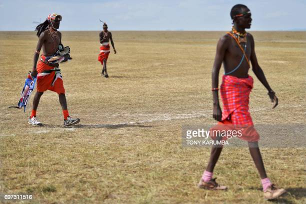Maasai warriors leave the pitch following a match against the British Army Training Unit Kenya team on June 18 2017 during a cricket tournament...
