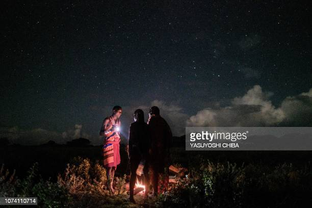 TOPSHOT Maasai warriors prepare their dinner at the site of a sporting event dubbed the Maasai Olympics at Kimana near Kenya's bordertown with...