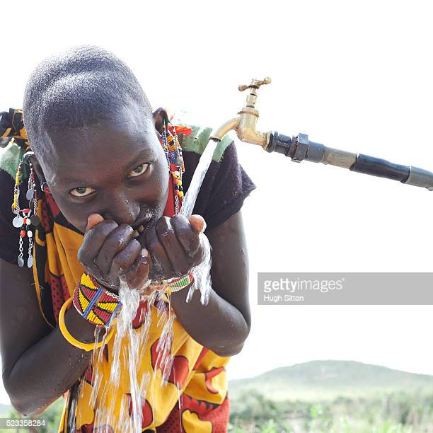 Maasai woman drinking from tap