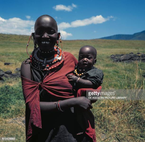 Maasai woman holding a baby and wearing traditional clothes and jewels Kenya