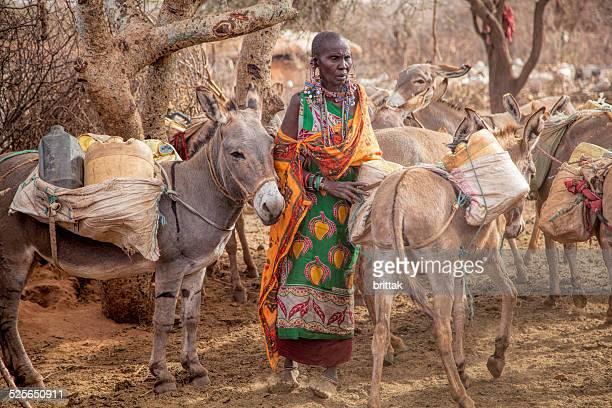 Mujer Maasai carga burro para recoger agua.