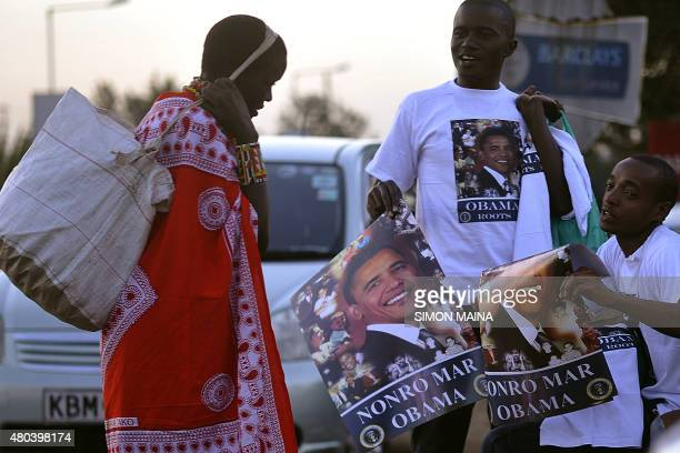 A Maasai woman looks at hawkers selling a poster of US President Barrack Obama and the words written in the Luo language 'Nonro Mar Obama' meaning...