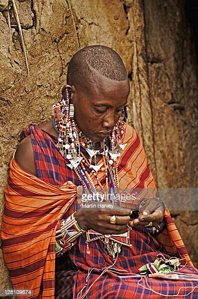 maasai woman sits outside entrance to home making beaded jewelry. (mikatei tajeu) near amboseli national park, kenya - eastern african tribal culture stock photos and pictures