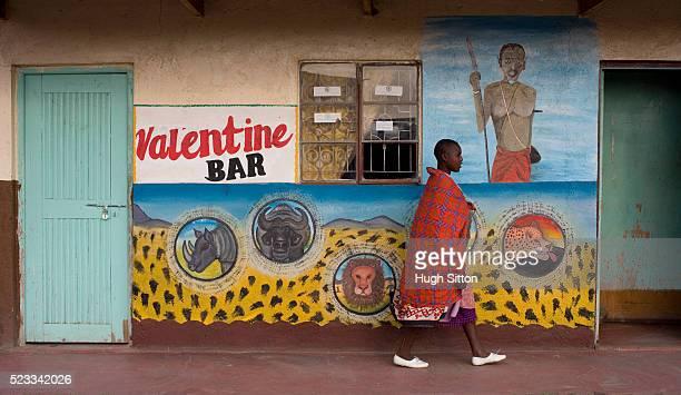 maasai woman walking past typical kenyan bar - hugh sitton stock pictures, royalty-free photos & images
