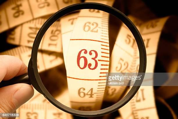 Maßband mit der Zahl 63 unter der Lupe Symbolfoto Rente mit 63