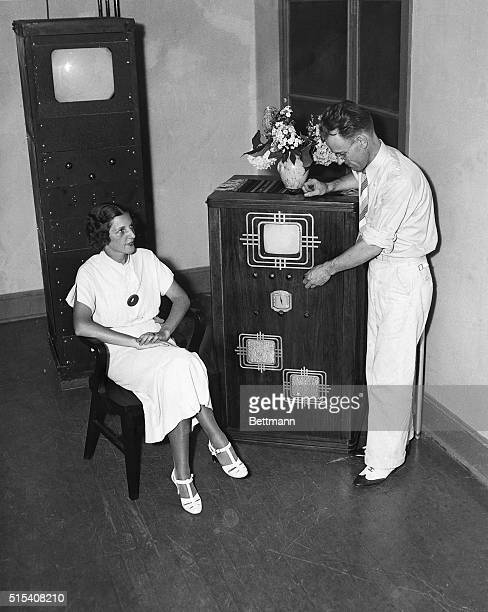 Mabel Bernstein watches as Philo T Farnsworth tunes the combination radio and television receiving set that he developed and demonstrated to a group...