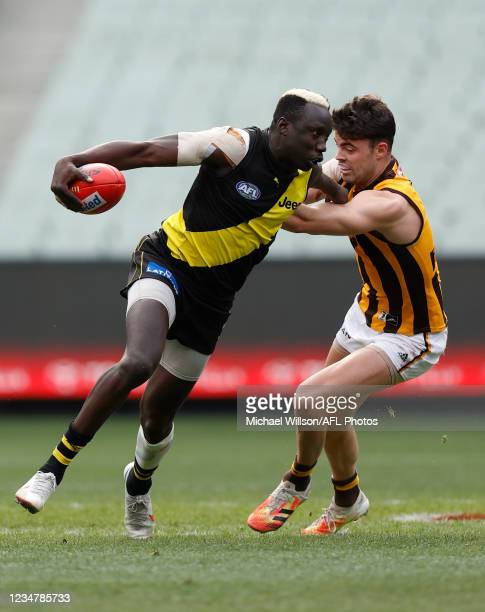 Mabior Chol of the Tigers is tackled by Conor Nash of the Hawks during the 2021 AFL Round 23 match between the Richmond Tigers and the Hawthorn Hawks...