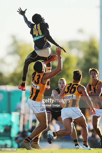 Mabior Chol of the Tigers leaps early on Marc Pittonet of the Hawks in a ruck contest during the 2016 AFL NAB Challenge match between the Richmond...