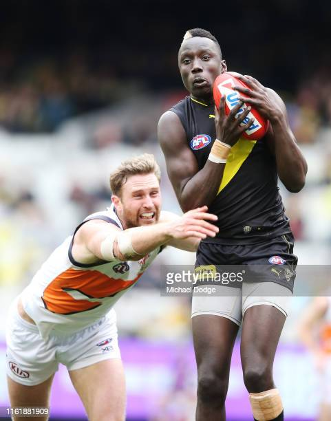 Mabior Chol of the Tigersmarks the ball against Dawson Simpson of the Giants during the round 17 AFL between the Richmond Tigers and the Greater...