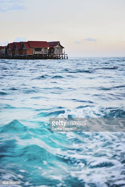 mabul island village at sunset - mabul island stock photos and pictures
