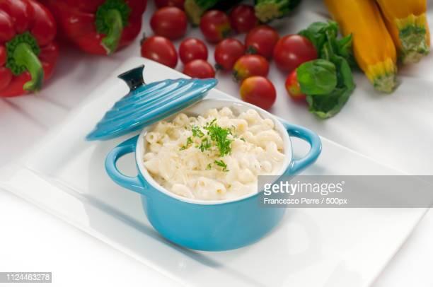 mac and cheese on a blue little clay pot - crosta di formaggio foto e immagini stock