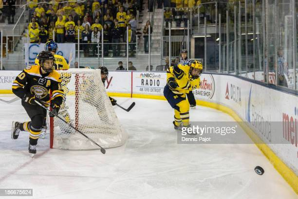Mac Bennett of the Michigan Wolverines fires the puck past Tanner Kero of the Michigan Tech Huskies on November 2 2013 at Yost Ice Arena in Ann Arbor...