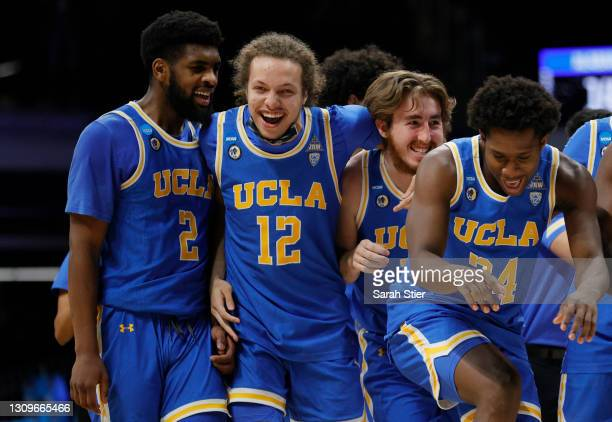 Mac Etienne of the UCLA Bruins celebrates with Jake Kyman and Cody Riley after defeating the Alabama Crimson Tide in the Sweet Sixteen round game of...