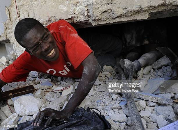 Mac Fanieh tries to rescue a live teacher trapped amid the rubble of the earthquake as he crawls past a schoolgirl that died at Ecole St Gerard on...