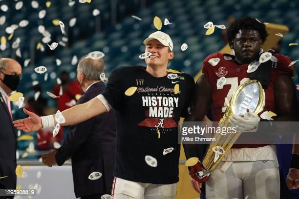 Mac Jones of the Alabama Crimson Tide celebrates alongside Alex Leatherwood following their win over the Ohio State Buckeyes in the College Football...