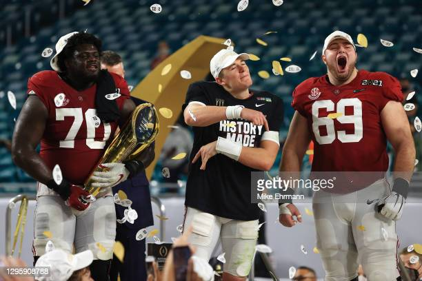 Mac Jones of the Alabama Crimson Tide celebrates alongside Landon Dickerson and Alex Leatherwood following their win over the Ohio State Buckeyes in...