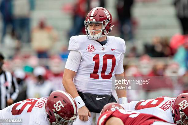 Mac Jones of the Alabama Crimson Tide looks over the defense at the line of scrimmage during a game against the Arkansas Razorbacks at Razorback...