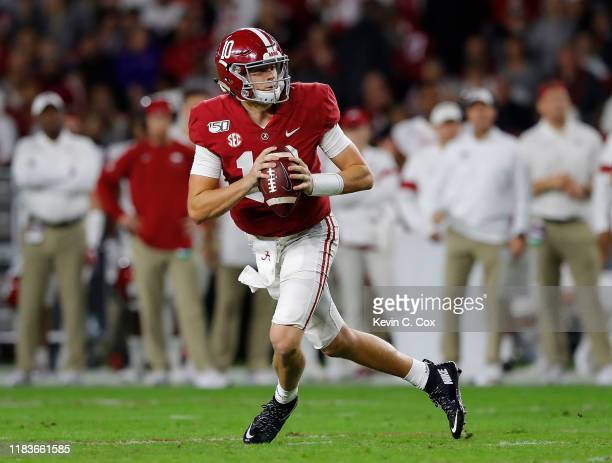 Mac Jones of the Alabama Crimson Tide rolls out of the pocket against the Arkansas Razorbacks in the first half at Bryant-Denny Stadium on October...