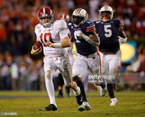 Mac Jones of the Alabama Crimson Tide rushes away from the Auburn Tigers in the second half at Jordan Hare Stadium on November 30 2019 in Auburn...