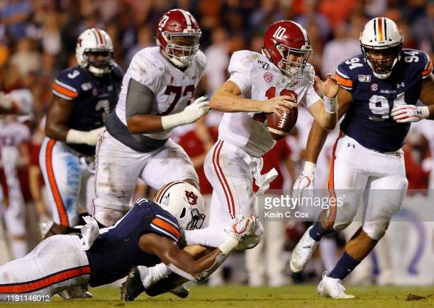 Mac Jones of the Alabama Crimson Tide rushes upfield as he is tackled by Big Kat Bryant of the Auburn Tigers at Jordan Hare Stadium on November 30...