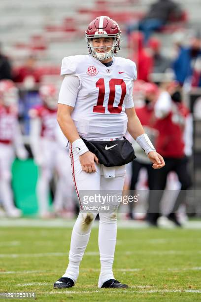 Mac Jones of the Alabama Crimson Tide smiles while looking at the sidelines during a game against the Arkansas Razorbacks at Razorback Stadium on...