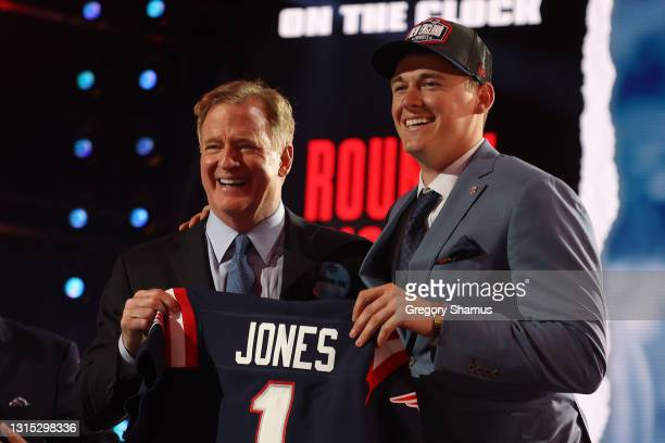 Mac Jones poses with NFL Commissioner Roger Goodell onstage after being selected 15th by the New England Patriots during round one of the 2021 NFL...