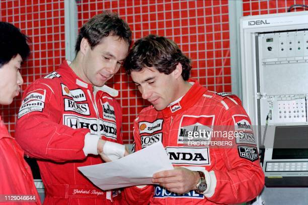 Mac Laren's drivers Gerhard Berger of Austria and Brazilian Ayrton Senna check their time after a practise session on May 16 1991 on the race track...