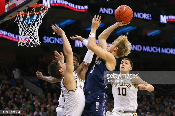 Mac McClung of the Georgetown Hoyas attempts a shot as Jeremiah RobinsonEarl Saddiq Bey and Cole Swider of the Villanova Wildcats defend during the...
