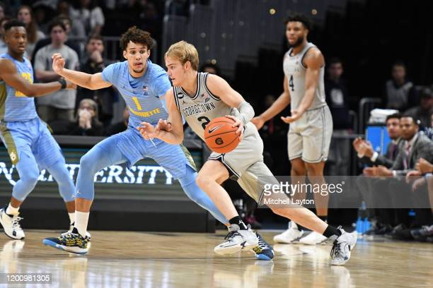Mac McClung of the Georgetown Hoyas dribbles by Brendan Bailey of the Marquette Golden Eaglesduring a college basketball game at the Capital One...