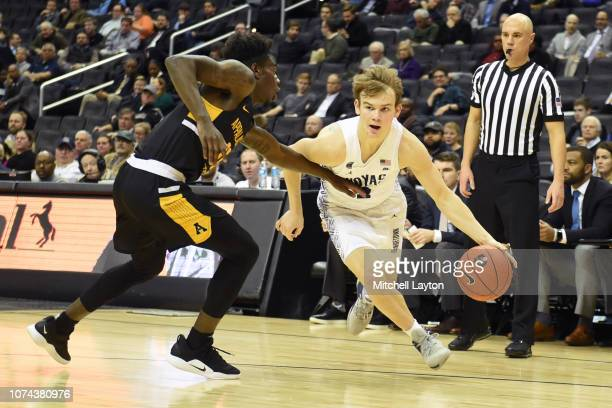 Mac McClung of the Georgetown Hoyas dribbles by Joseph Battle of the Appalachian State Mountaineers during a college basketball game at the Capital...