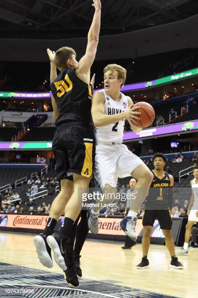 Mac McClung of the Georgetown Hoyas tries to pass the ball around Hunter Seacat of the Appalachian State Mountaineers during a college basketball...