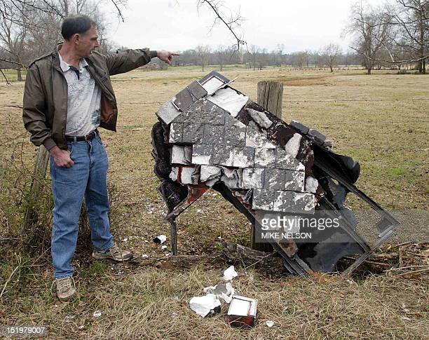 Mac Powell points to a portion of the space shuttle Columbia 03 February 2003 that fell onto his ranch after the shuttle broke up as it returned from...