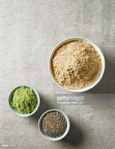maca powder, barley sprouts powder and chia seeds in various bowls (seen from above) - maca plant stock photos and pictures