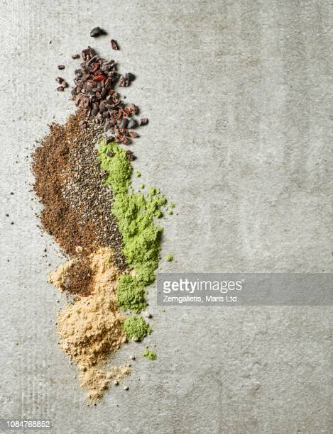 maca powder, barley sprouts powder, chia seeds, ground flax seeds and cacao nibs on a grwy table - maca plant stock photos and pictures