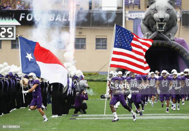 Macan Wilson of the Northwestern Wildcats runs on to the field with the state flag of Texas as teammate Montre Hartage carries the American flag...