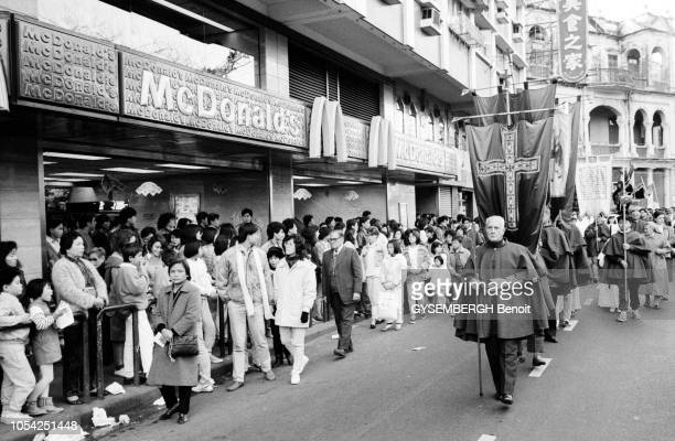Macao Janvier 1988 Le cortège d'une procession jésuite passant devant un restaurant Mc Donald's