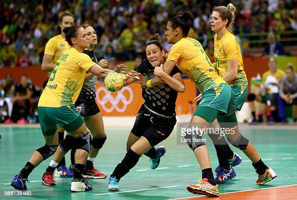 Macarena Diaz Aguilar of Spain is challenged by Daniela Piedade and Fabiana Diniz of Brazil during the Womens Preliminary Group A match between...
