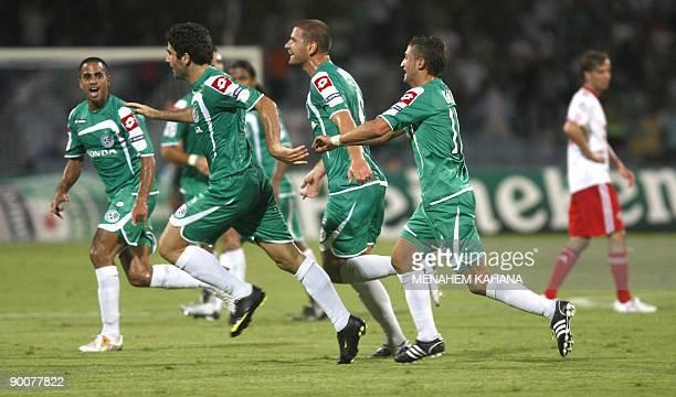 Maccabi Haifa's players celebrate their goal in the first half during their UEFA Champions League third round qualification return leg against...